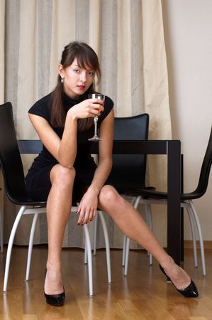 Beautiful woman in black dress with glass of red wine  Stock Photo - 4582633