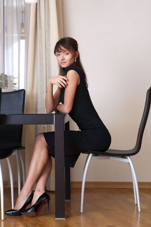 curved leg: Portrait of the beautiful woman in black dress. She is sitting at the table.