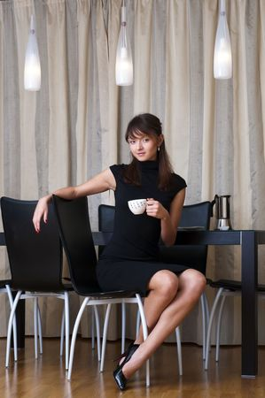 curved leg: Portrait of the beautiful woman. She is sitting in the restaurant with cup of coffee. Stock Photo