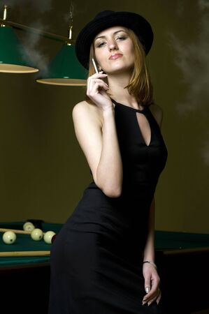 Portrait of the beautiful smoking woman in the billiards club photo
