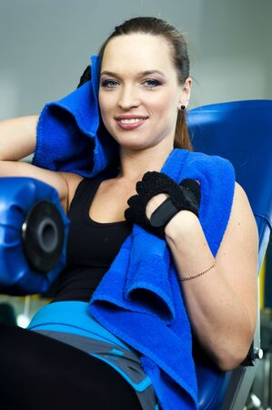 Portrait of the beautiful woman in the sport club. She is resting after exersises photo