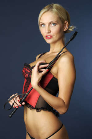 Portrait of the beautiful young blond lady with whip photo