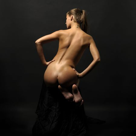 Back of the beautiful naked woman with dark background