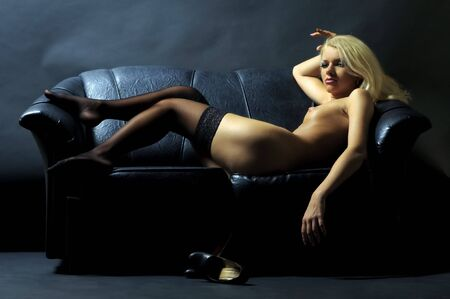 naked girl black hair: Beautiful blond is lying on the leather sofa Stock Photo