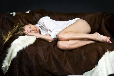 Portrait of the beautiful blonde. She is lying on the sofa photo