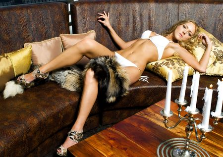 Portrait of the beautiful woman in beachwear. She is lying on the leather sofa photo