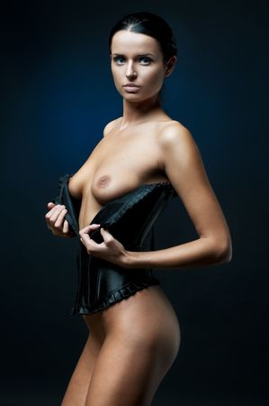 Portrait of the beautiful corseted woman with naked breast