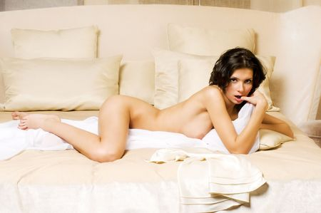Seductive beautiful naked woman is lying on a bed Stock Photo - 5652259