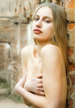 Portrait of the beautiful naked woman with brick background photo