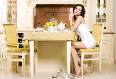 feet on desk: Rich beautiful woman is sitting at her kitchen and having a tea