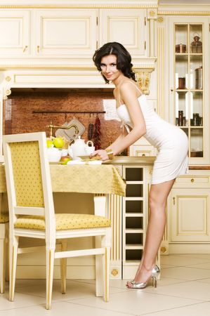 luxuriant: Rich beautiful woman is sitting at her kitchen and having a tea