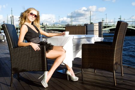 Beautiful woman in a black dress is sitting in the cafe at the river photo