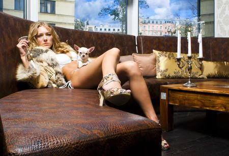 manteau de fourrure: Portrait de la belle blonde. Elle est assise dans le restaurant avec son chien