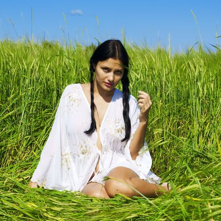 Portrait of the beautiful woman sitting at the rye field photo