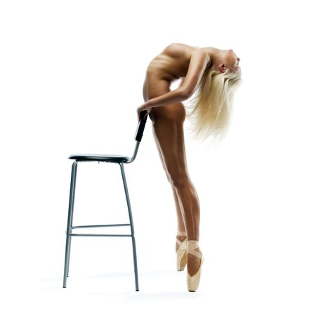 Nude ballerina is dancing at the chair