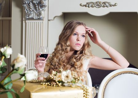 Portrait of the beautiful blonde. She is sitting with glass of red wine photo
