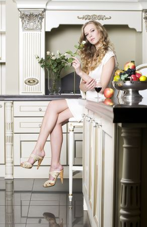 Beauttiful blonde is smelling a rose at her kitchen photo