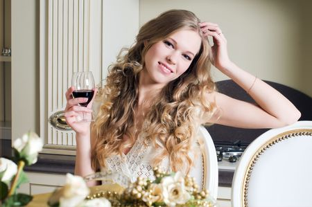 lux: Portrait of the beautiful blonde. She is sitting with glass of red wine