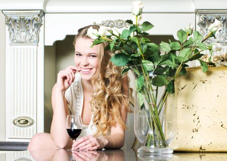 Portrait of the beautiful blonde with flowers at her kitchen photo