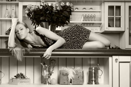 Portrait of the beautiful blonde. She is lying on the kitchen table. Monochrome image photo