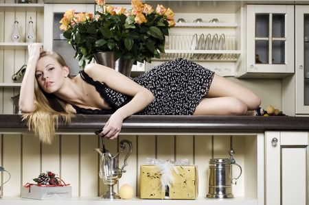Portrait of the beautiful blonde. She is lying on the kitchen table photo