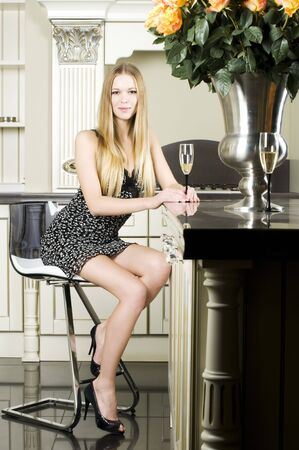Portrait of the beautiful woman. She is sitting at her kitchen with glass of champagne photo