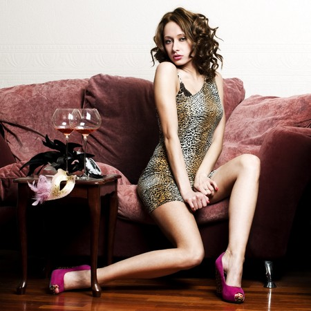 beautiful sexy woman in is sitting on the sofa with glass of red wine.