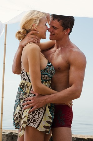 Young beautiful couple are kissing on the beach photo