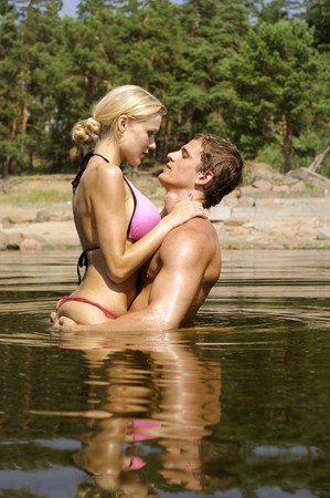 seduction: Young beautiful  couple are kissing in the water