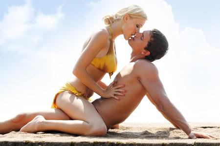 novios besandose: Joven pareja hermosa est� bes�ndose en la playa  Foto de archivo