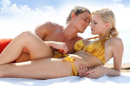 heterosexual couples: Young beautiful couple are holding on the beach Stock Photo