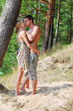 Young beautiful couple are kissing at the beach photo