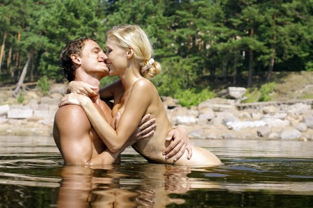 Young beautiful couple are kissing and holding in the water Stock Photo