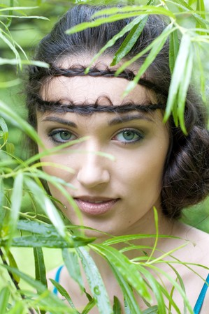 Portrait of the beautiful woman into the green trees photo