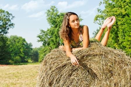 Rural landscape with Young beautiful woman at the haystack  photo
