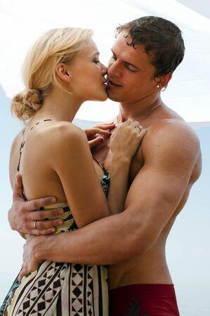 personas besandose: Joven pareja hermosa est� bes�ndose en la playa  Foto de archivo