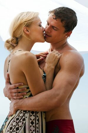 love kissing: Young beautiful couple are kissing on the beach Stock Photo