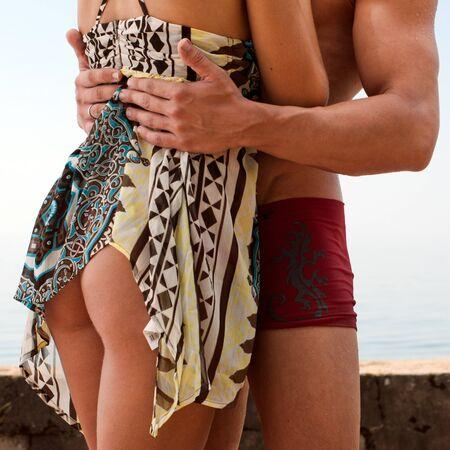 nalga: Joven pareja hermosa est� bes�ndose en el mar