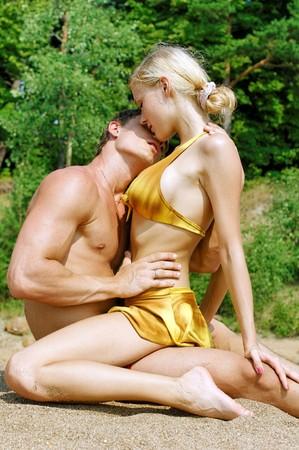 열정: Young beautiful couple are kissing on the beach 스톡 사진