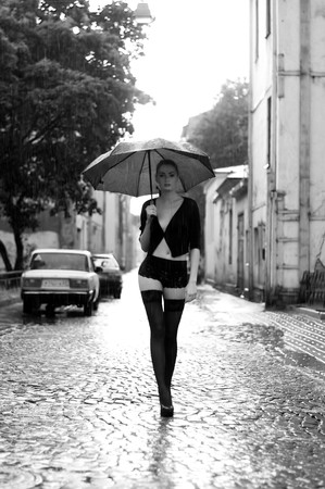 Potrait of the beautiful woman walking in the rain. Monochrome image photo