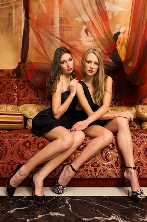 smooch: Two beautiful women are sitting on the sofa in a oriental interior Stock Photo