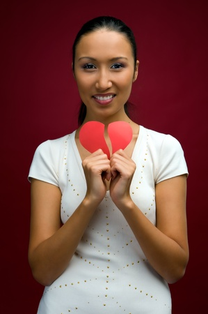 Young beautiful woman with broken heart in her hands photo