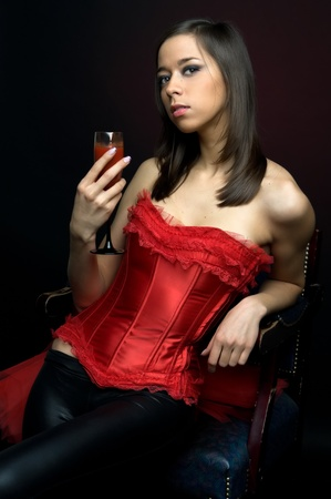 Portrait of the beautiful woman in red lingerie with glass of tomato juice photo