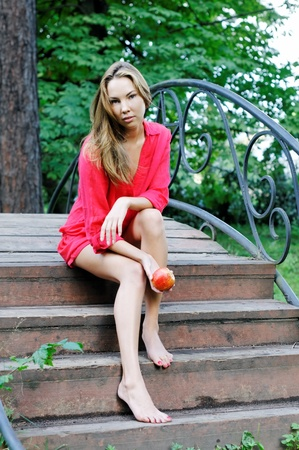 Portrait of the beautiful woman in a red dress outdoors photo