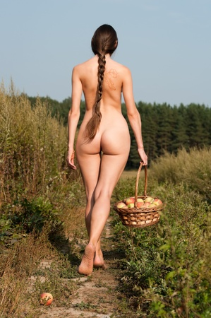 Rural scene. Beautiful naked woman on the field