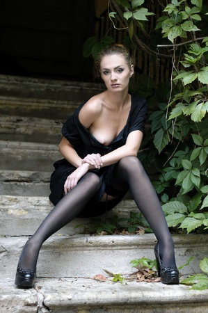 naked breast: Portrait of the beautiful woman with naked breast. She is sitting on the stairs.