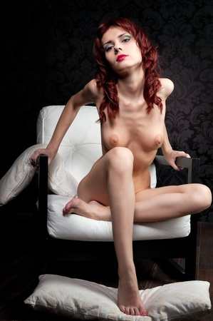 Young beautiful naked woman sitting on the armchair Stock Photo - 9380239