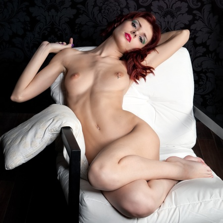 Young beautiful naked woman sitting on the armchair