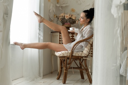 Portrait of the beautiful woman drinking tea in the morning