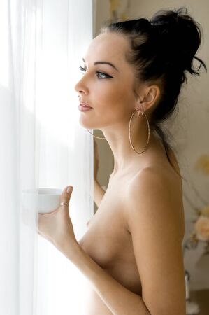 woman bra: Portrait of the beautiful woman. She is drinking tea at the window